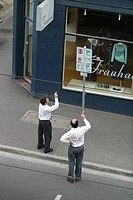 Businessmen Attempting to Figure Out Parking Sign