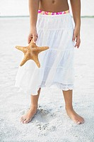 Girl on beach holding starfish
