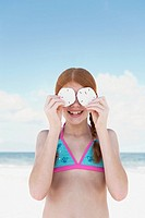 Girl on beach holding sand dollars over eyes