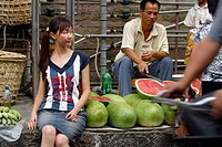 Asian model with watermelon seller behind