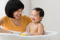 Asian mother washing her daughter in bathtub