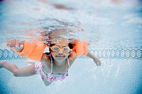 Hispanic girl swimming underwater in pool