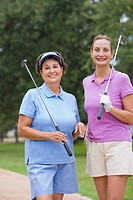 Mature woman holding golf clubs