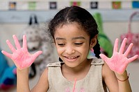 Close_up of a girl showing paint covered hands and smiling