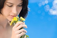 Close_up of a young woman holding a bunch of flowers and smelling