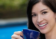 Portrait of a young woman drinking tea and smiling