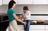 Side profile of a young woman preparing food with her daughter in the kitchen