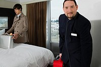 Portrait of a room service man holding a luggage with a businessman looking at a briefcase