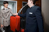 Room service man handing over luggage to a businessman (thumbnail)