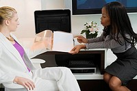 Businesswoman showing a file to another businesswoman