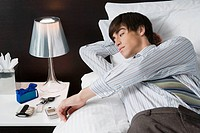 Businessman lying on the bed and looking at a mobile phone