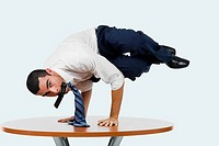 Portrait of a businessman doing a handstand on a table with a mobile phone in his mouth