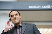Businessman talking on a hands free device at an airport