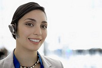 Portrait of a businesswoman wearing a hands free device and smiling (thumbnail)