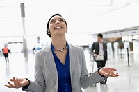Businesswoman laughing in a hands free device at an airport lounge (thumbnail)