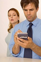 Portrait of a man using his PDA while a woman peeks over his shoulder.