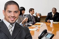 Portrait of a businessman smiling with his colleagues discussing in the background (thumbnail)