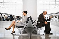 Side profile of a businesswoman using a laptop and a businessman using a mobile phone at an airport