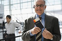 Close-up of a businessman putting a passport with an airplane ticket in his coat's pocket (thumbnail)