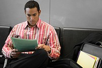 Businessman reading a file in the waiting room of an airport