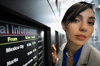 Portrait of a businesswoman in front of an arrival departure board at an airport