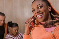 Portrait of a young woman talking on a mobile phone and smiling (thumbnail)