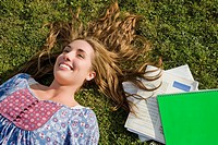 High angle view of a young woman lying in a lawn