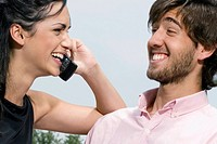 Young woman talking on a mobile phone with a young man smiling (thumbnail)