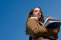 Low angle view of a young woman holding textbooks