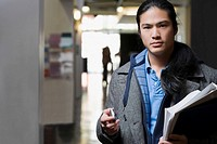 Portrait of a young man holding textbooks and a mobile phone