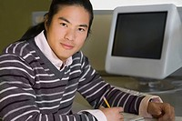 Portrait of a young man sitting in a computer lab and studying
