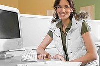 Portrait of a young woman sitting in front of a desktop PC and smiling (thumbnail)