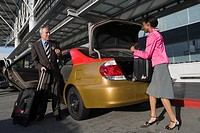 Side profile of a businesswoman loading her suitcase on a car trunk with a businessman standing in front of her