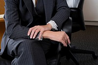 Mid section view of a businesswoman sitting on a chair