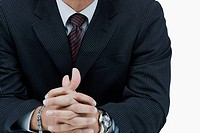 Mid section view of a businessman with his hands clasped