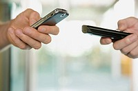 Close_up of two people using their mobile phones