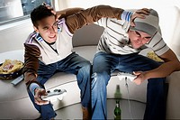 High angle view of two young men playing video game and rough housing