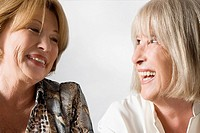 Close_up of two senior woman looking at each other and smiling