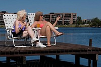 Two senior women sitting on chairs at the boardwalk