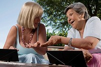 Two senior women playing games and smiling (thumbnail)