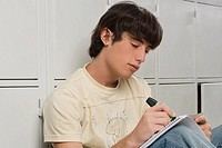 Close_up of a young man writing with a highlighter
