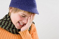 Close_up of a boy covering his eyes with his hands