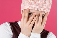 Close_up of a girl hiding her face with her hands