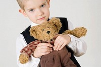 Close_up of a boy holding a teddy bear
