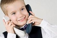 Close_up of a boy talking on two landline phones