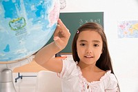 Portrait of a schoolgirl pointing on a globe