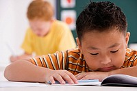 Close_up of a schoolboy reading a book in a classroom