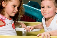 Side profile of a boy and a girl sitting in a toy car