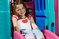 Portrait of a girl sitting on a slide and smiling