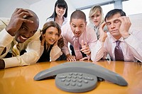 Business executives looking at the conference phone